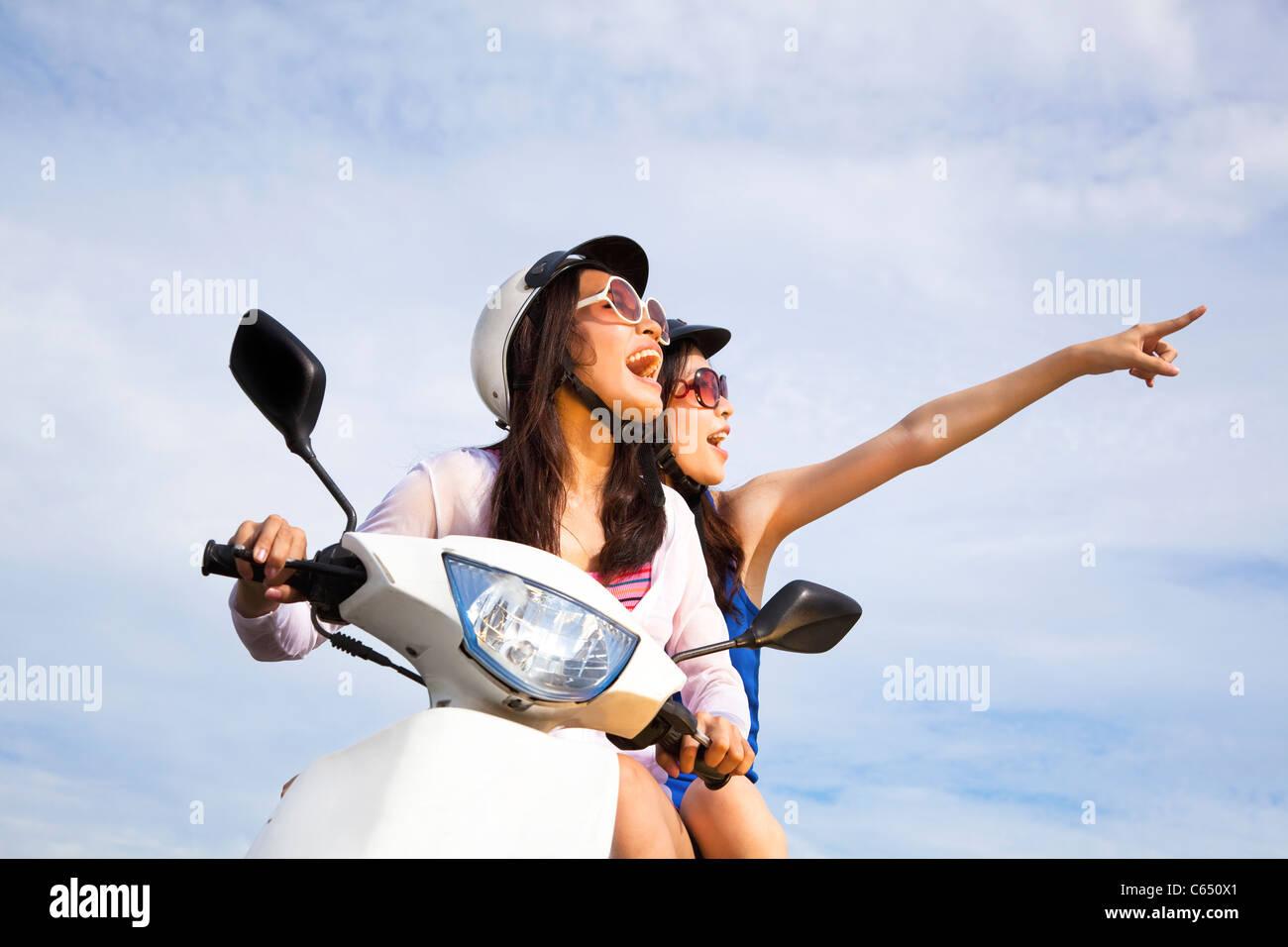 Felice ragazze scooter equitazione godetevi la vacanza estiva Immagini Stock