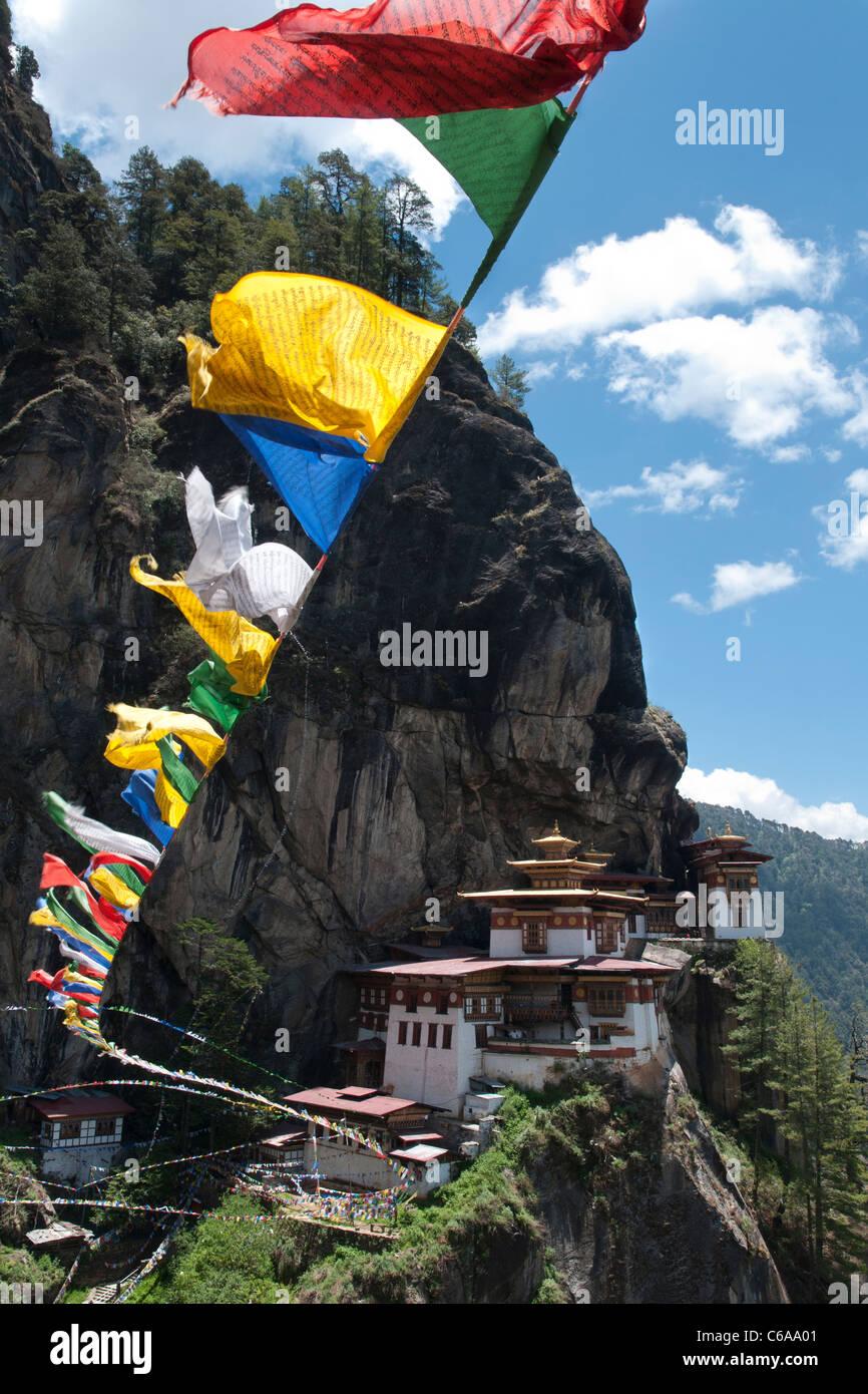 Taktshang Goemba. Tigri nest monastero. vista con la preghiera le bandiere e cliff. Paro valley, Bhutan Foto Stock