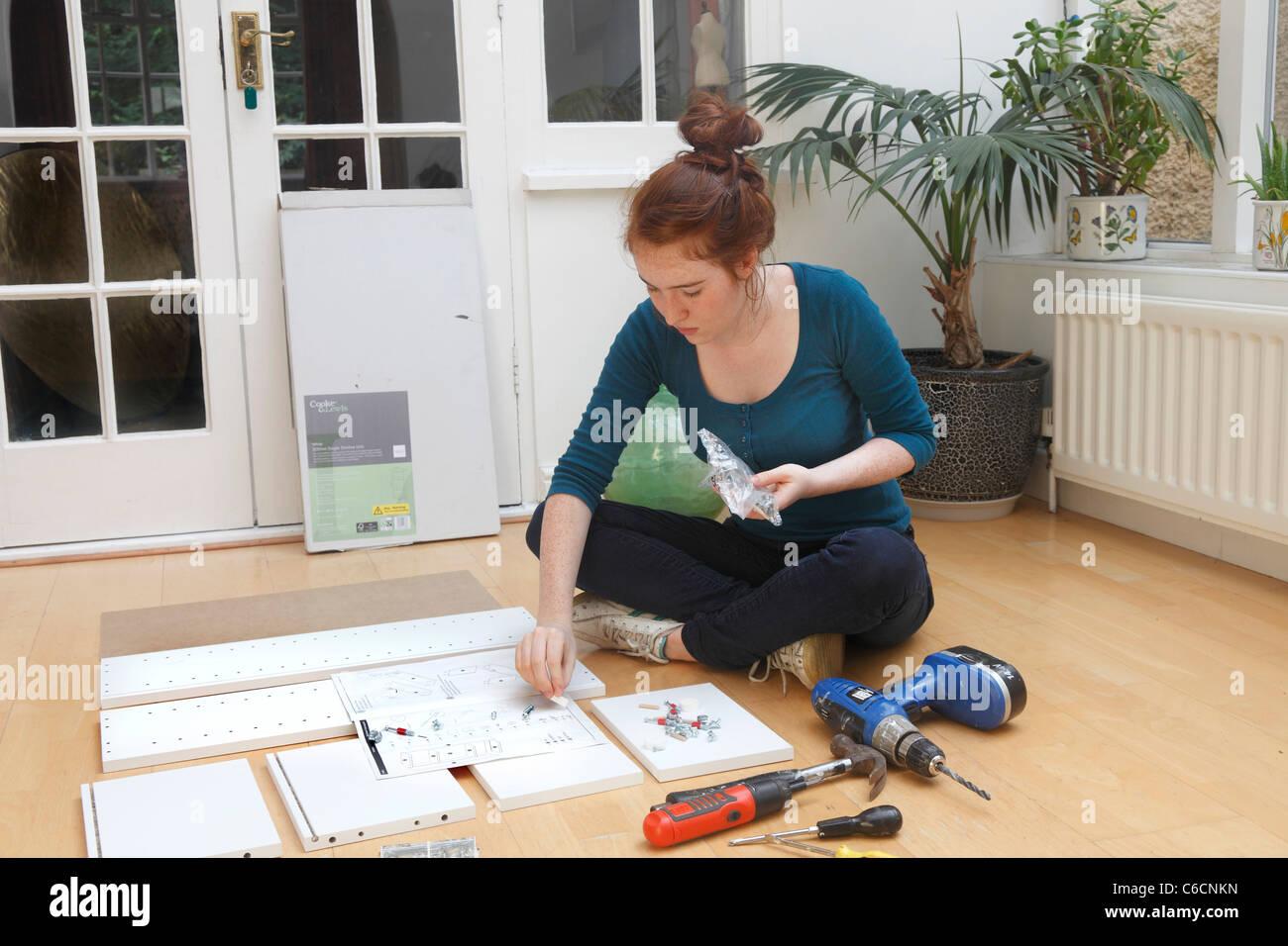 Ragazza giovane rendendo un armadio da un 'Flat Pack' kit DIY. Immagini Stock