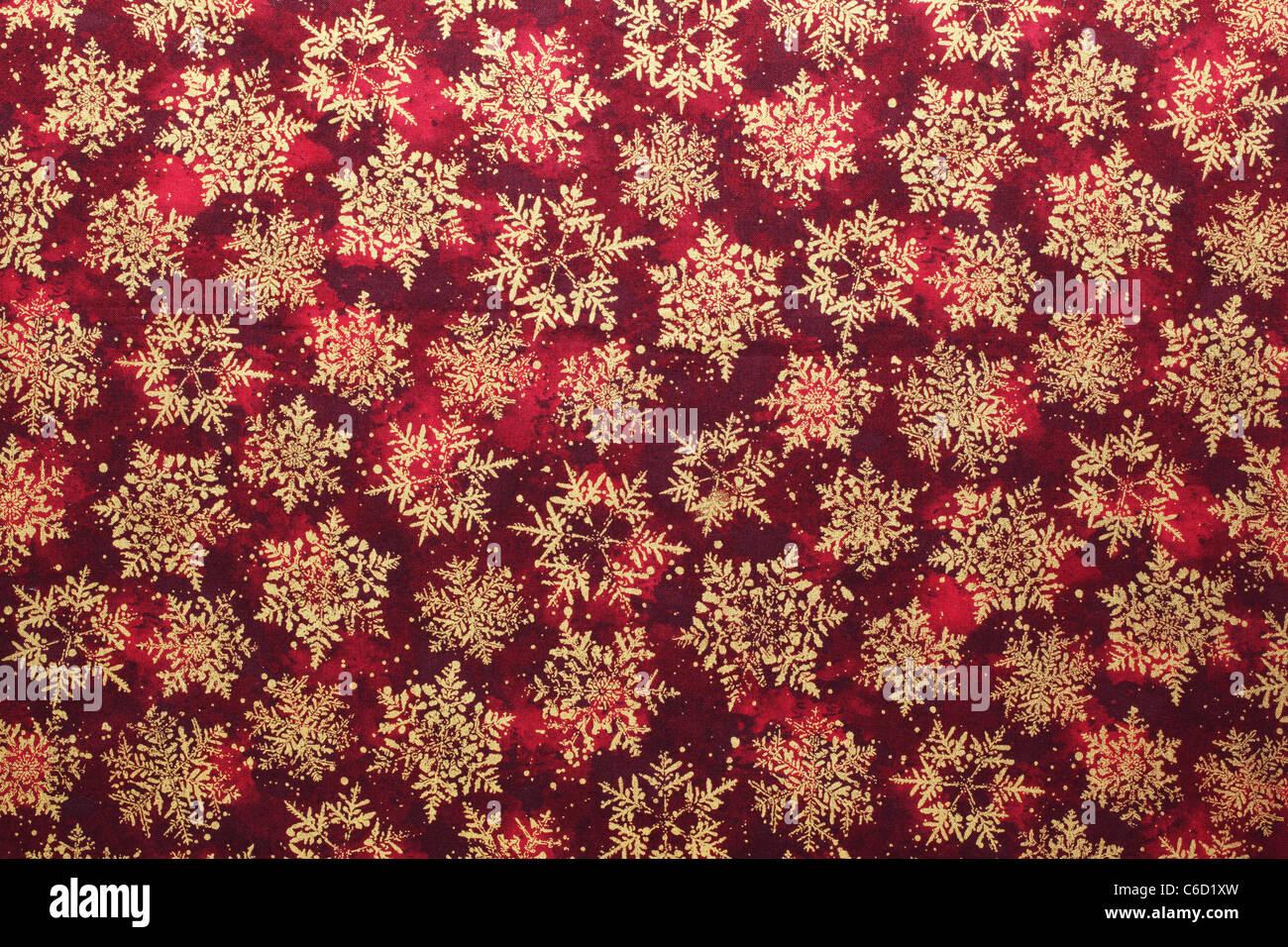 Golden schema a fiocco di neve sullo sfondo del tessuto. Immagini Stock