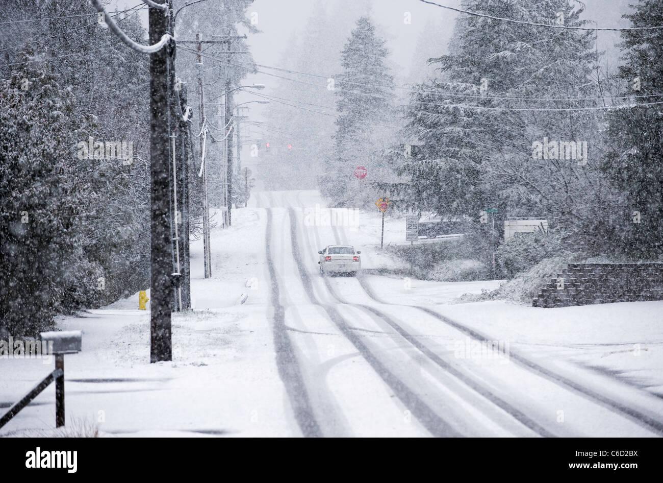 Guida auto sulla strada residenziale durante la tempesta di neve, Seattle, Washington, Stati Uniti d'America Immagini Stock