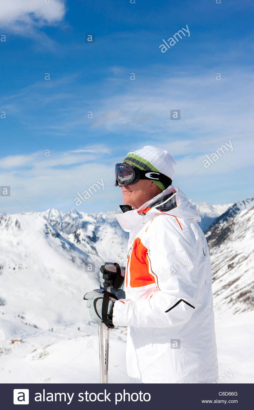 Uomo sorridente indossando occhiali da sci e azienda bastoncini da sci sulla montagna innevata Immagini Stock