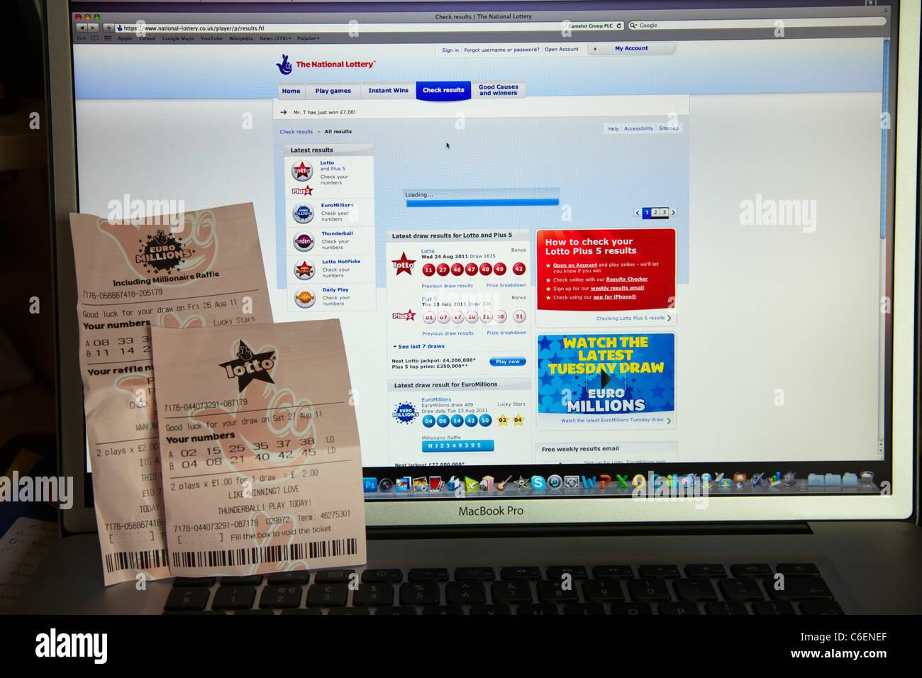 Regno Unito biglietti della lotteria essendo controllato on-line di internet e del lotto in milioni di euro numeri Immagini Stock