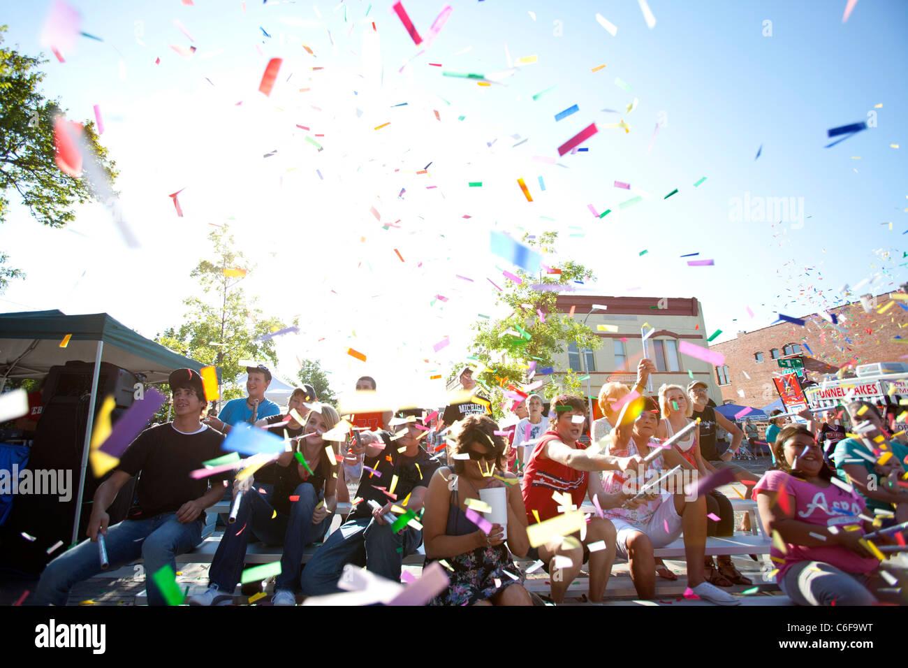 Un gruppo di persone lancio coriandoli in aria durante un festival di kick-off cerimonia in Rogers, Arkansas. Immagini Stock