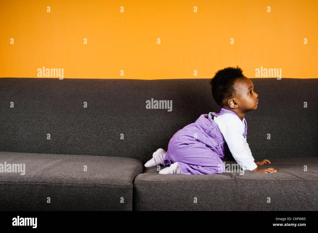 Una bambina su un divano Immagini Stock