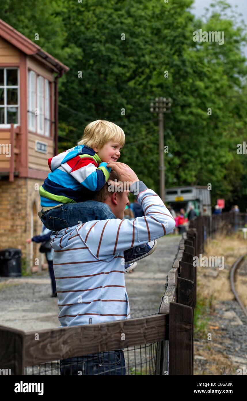 Uomo che porta il suo giovane figlio sulle sue spalle Immagini Stock