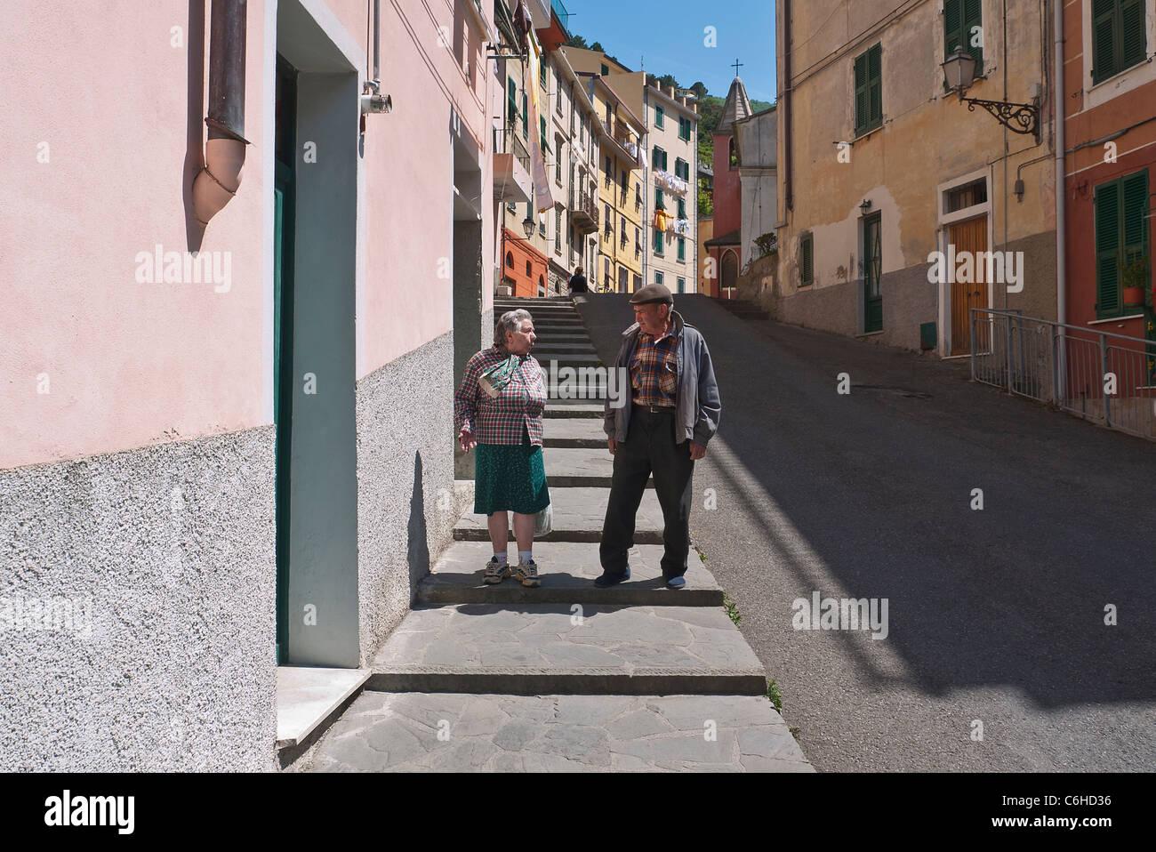 Un anziana coppia italiana parla e gesto come essi camminare sul marciapiede nel loro villaggio di Riomaggiore, Cinque Terre, Italia. Foto Stock