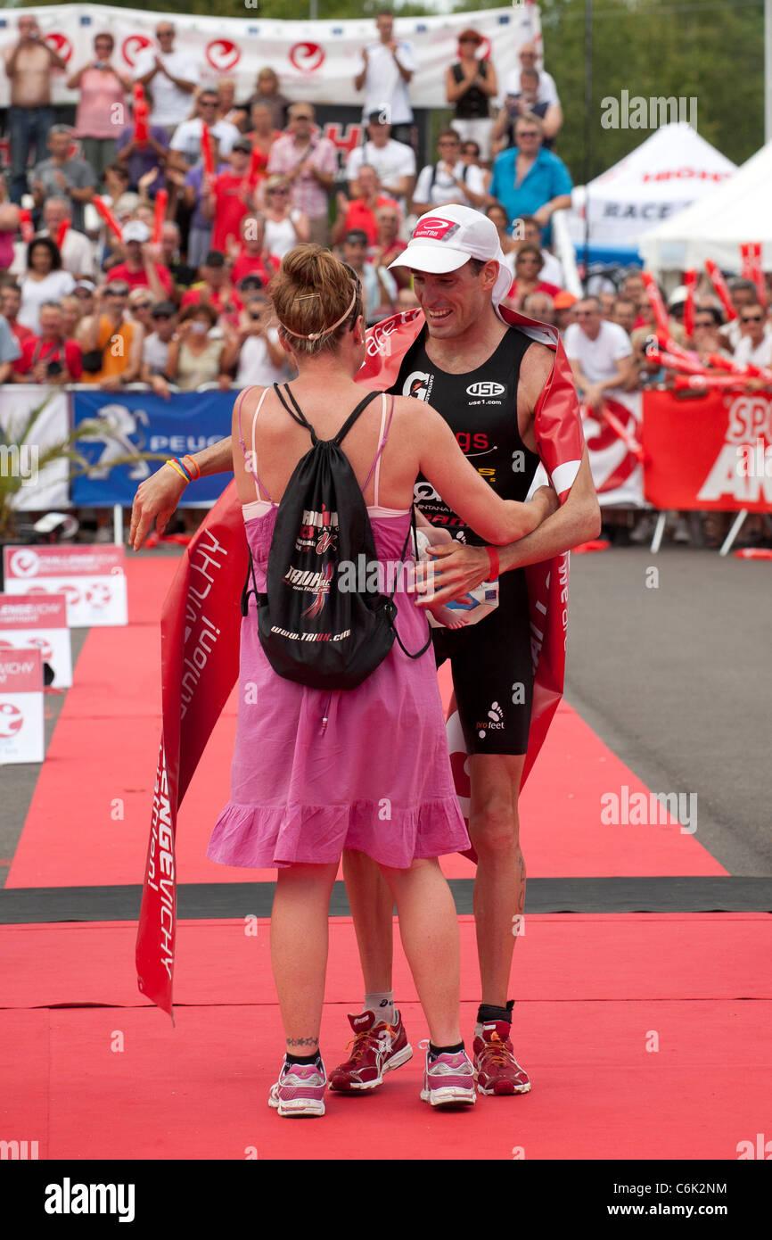 La Vichy piena distanza gara di triathlon vincitore Stephen Bayliss ha salutato dalla moglie. Immagini Stock