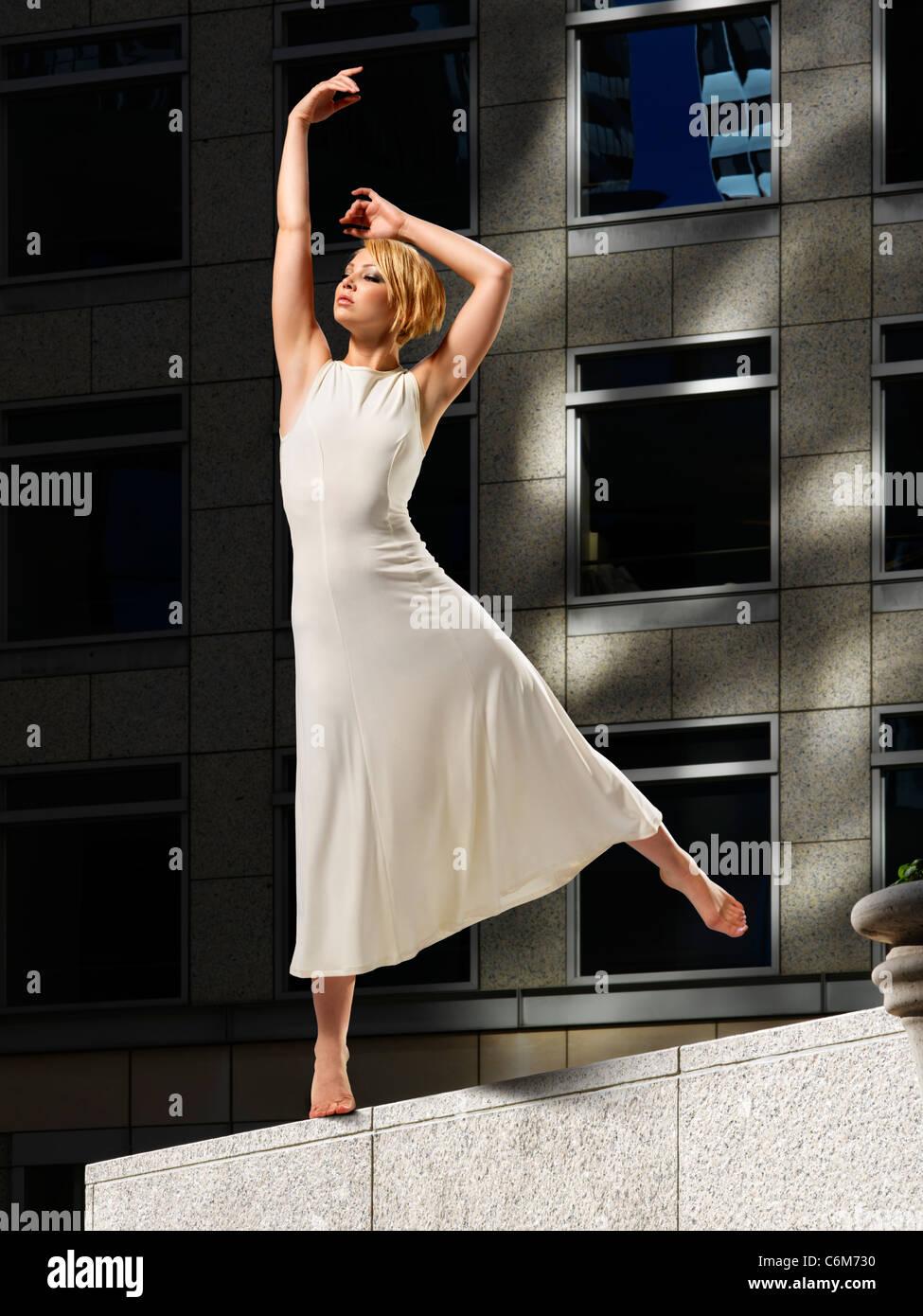 Donna ballerino in un sole luminoso posto sulla mensola di pietra di costruzione di ufficio plaza visto drammaticamente Immagini Stock