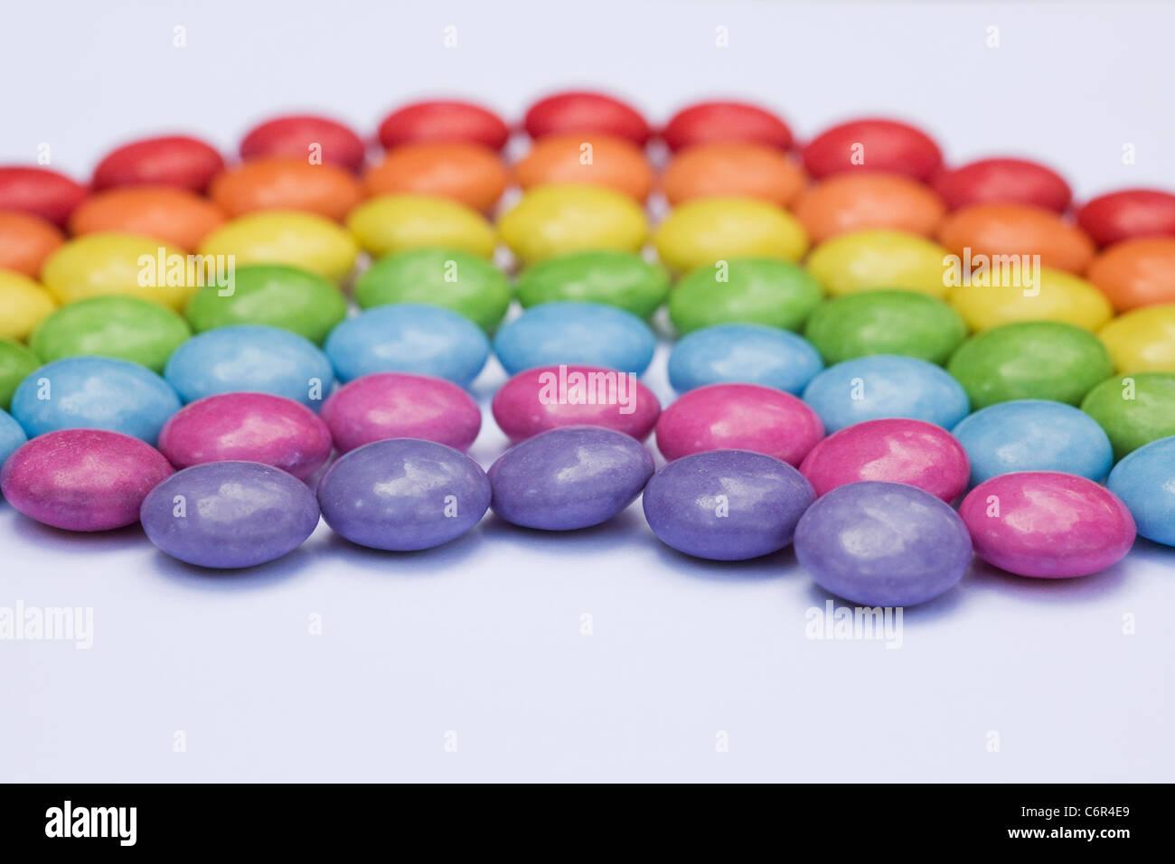 Rainbow smartie pattern su uno sfondo bianco. Immagini Stock