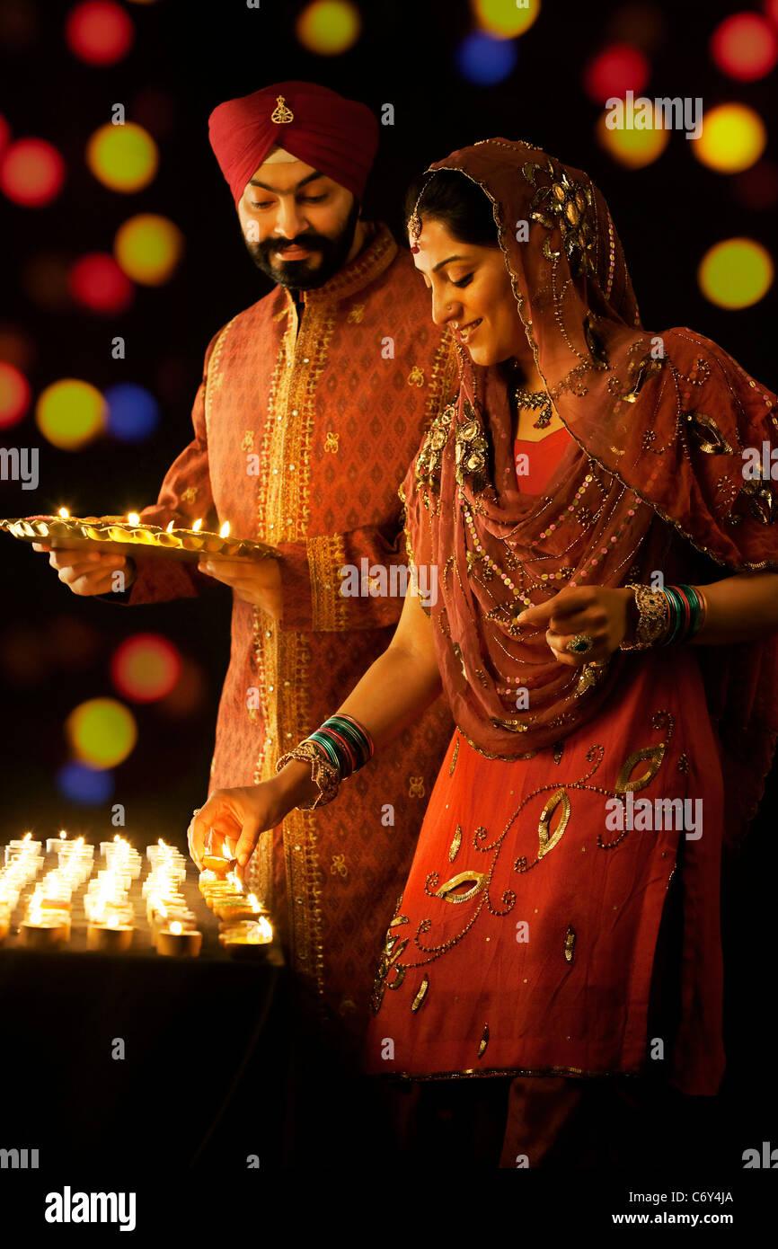 La religione sikh uomo tenendo un vassoio di diyas mentre la donna li pone su un tavolo Immagini Stock