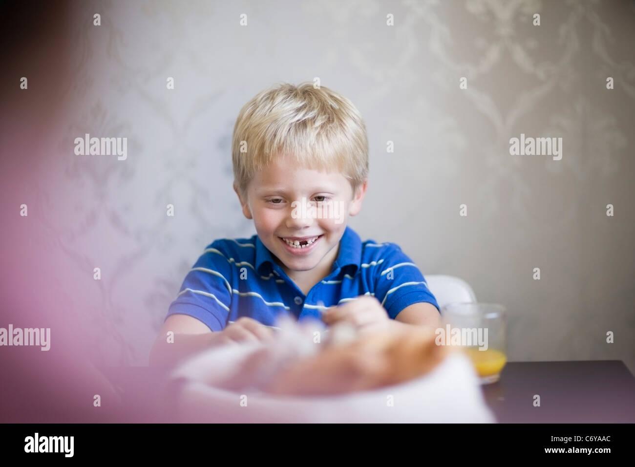Ragazzo che sorride al tavolo per la cena Foto Stock