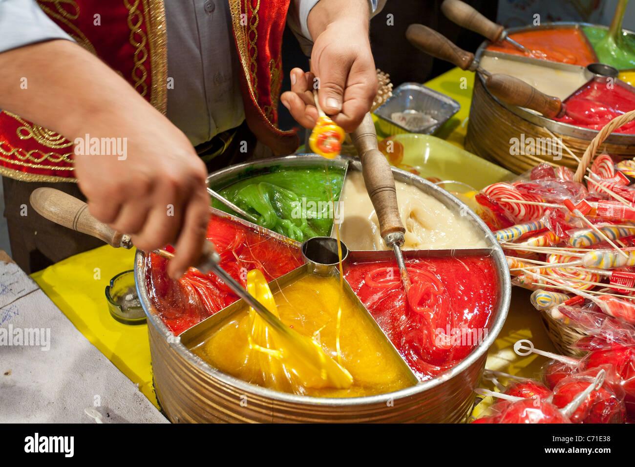Candy rendendo nel mercato. Le mani si muovono rapidamente la laminazione del metallo fuso caramelle multicolore Immagini Stock