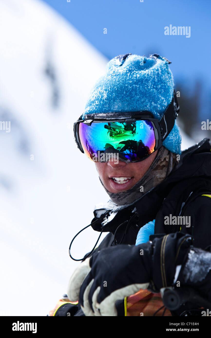 Un ritratto di uno snowboarder sorridente con un riflesso di una motoslitta su i suoi occhiali protettivi nel backcountry Immagini Stock
