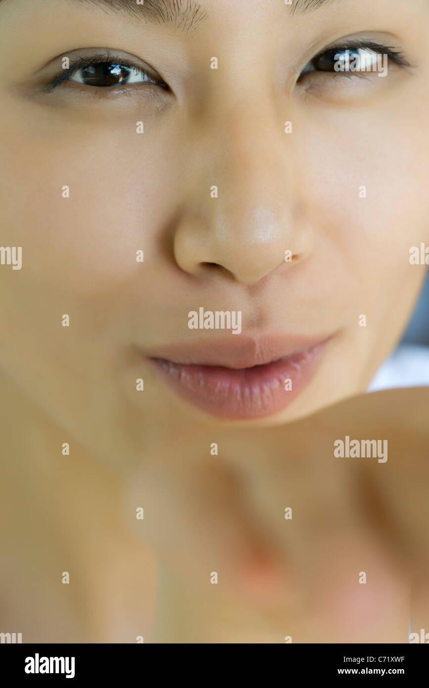 Giovane donna soffia un bacio alla fotocamera Immagini Stock
