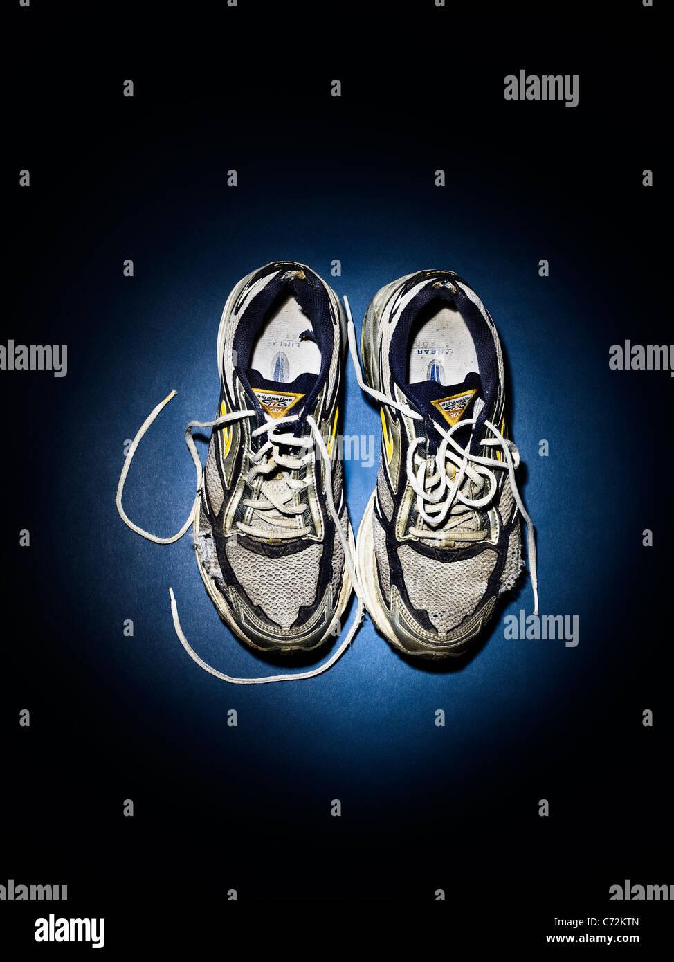 Vecchie scarpe da running, formatori in un faretto Immagini Stock