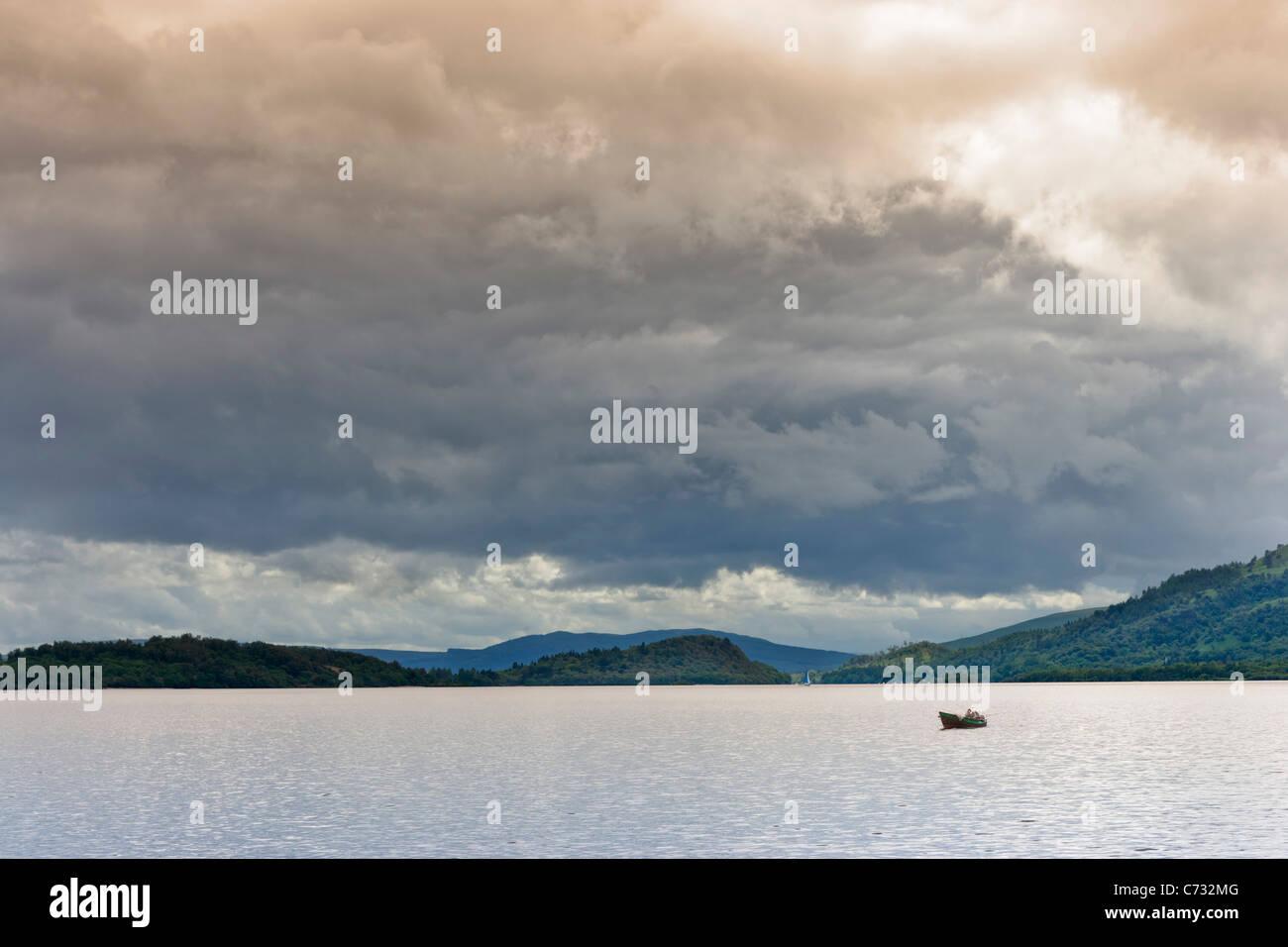 Piccola barca sul Loch Lomond preso dalla sponda orientale vicino a Rowardennan, Scotland, Regno Unito Immagini Stock