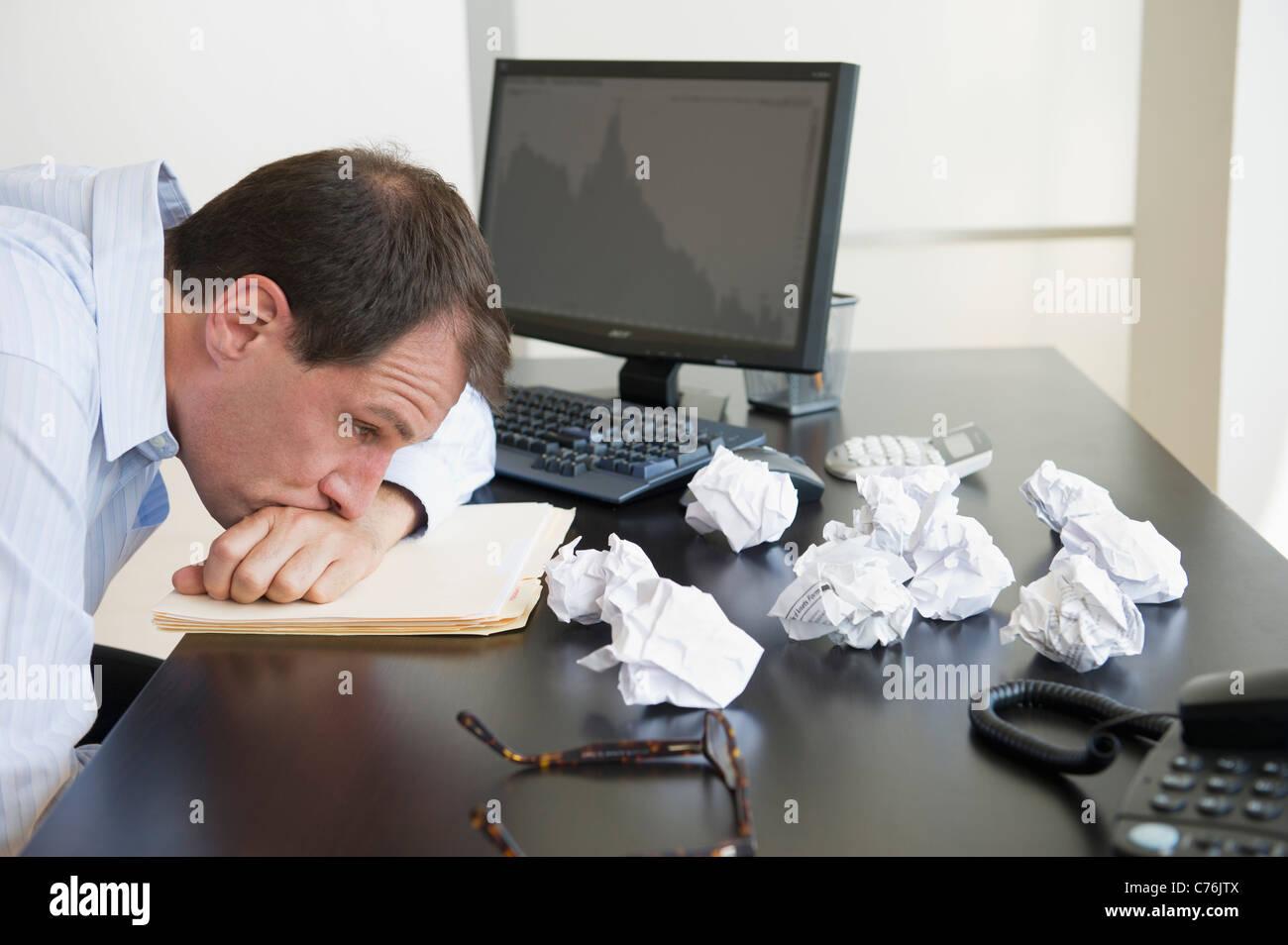 Stati Uniti d'America, New Jersey, Jersey City, imprenditore con a faccia in giù sulla scrivania Immagini Stock