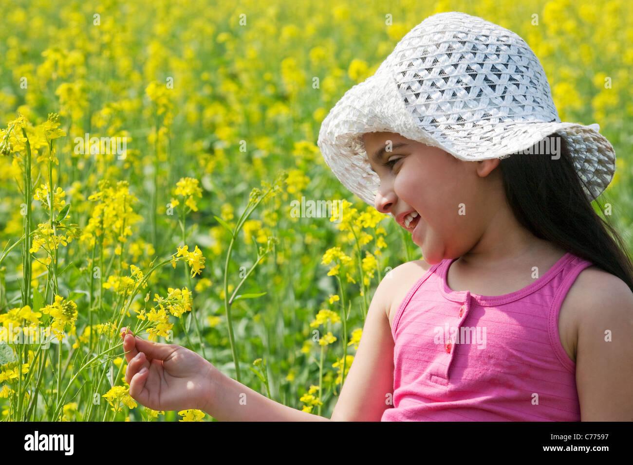 Ragazza giovane guardando i fiori Immagini Stock