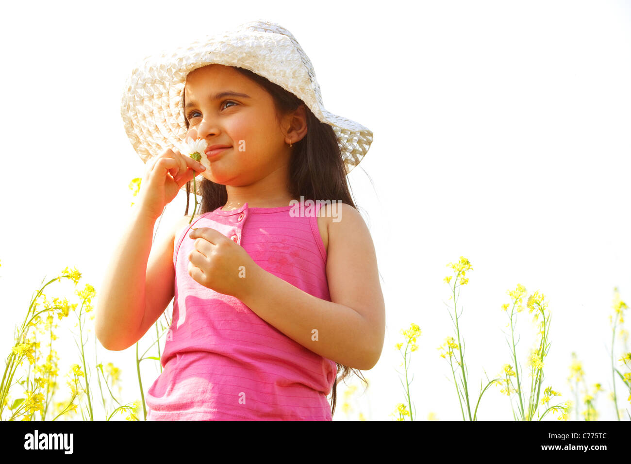 Ragazza giovane odorare un fiore Immagini Stock