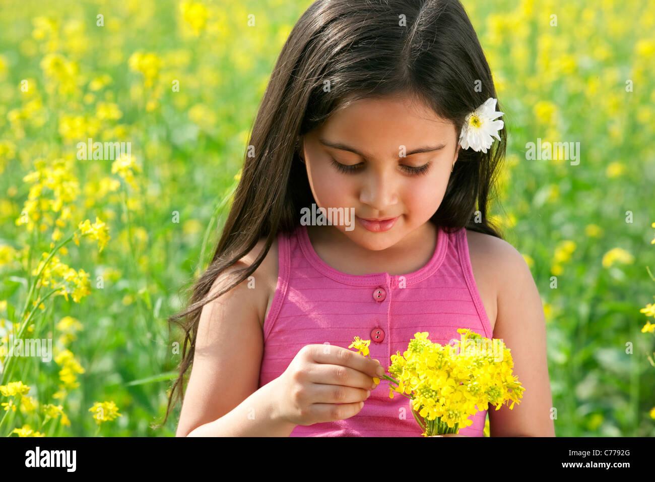 Ragazza giovane spiumatura fiori Immagini Stock