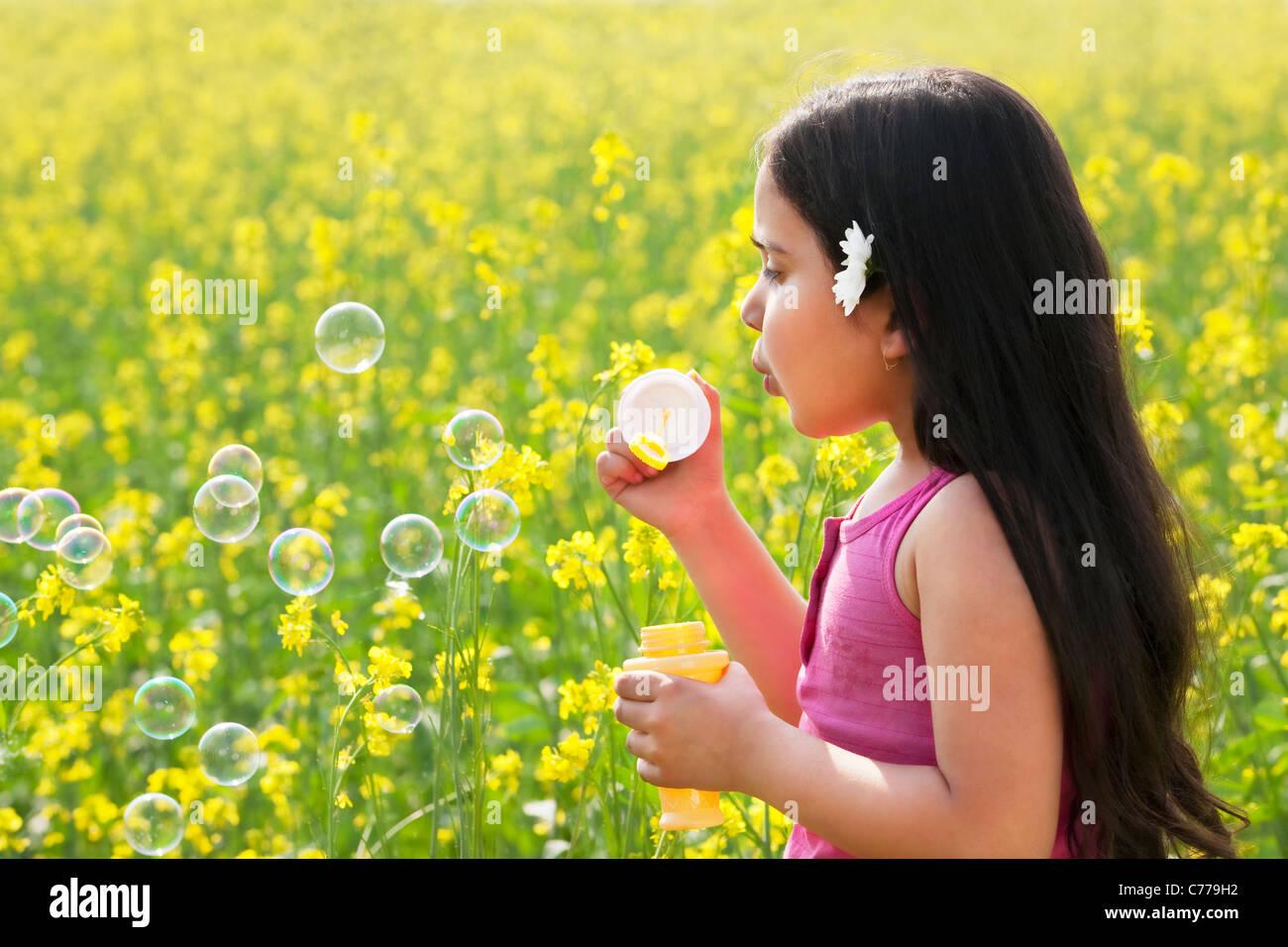 Ragazza giovane soffiare bolle in un campo Immagini Stock
