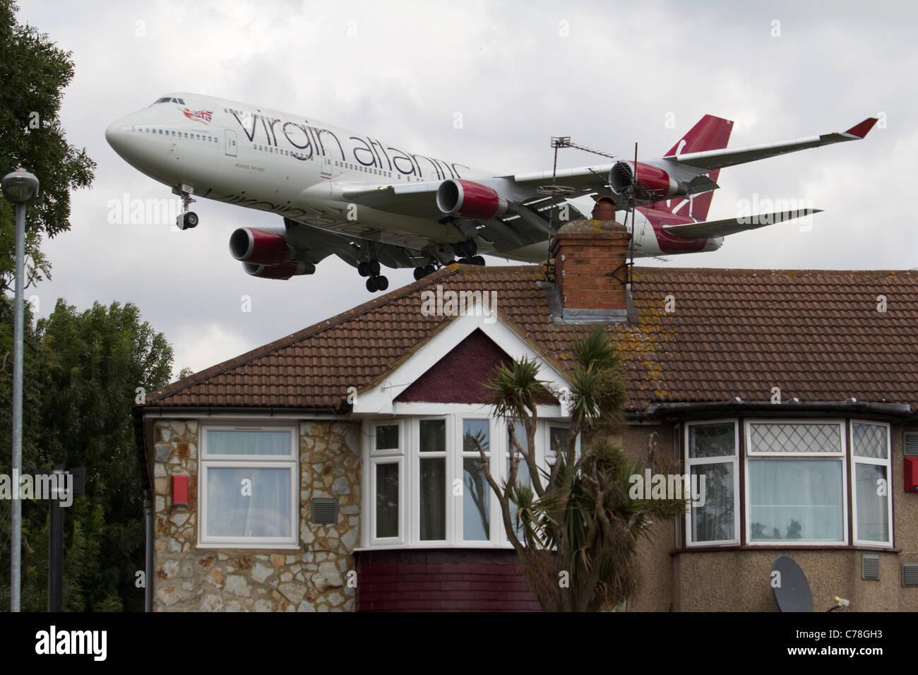 Bassa Battenti aereo aeroporto di Heathrow approccio Virgin Atlantic, inquinamento acustico con edilizia residenziale Immagini Stock