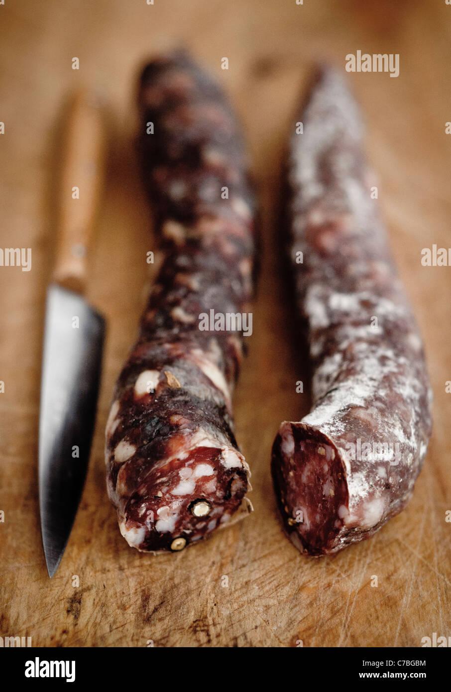 Artisan ha reso l'aria salsiccia secca su tavola di legno con il coltello Immagini Stock