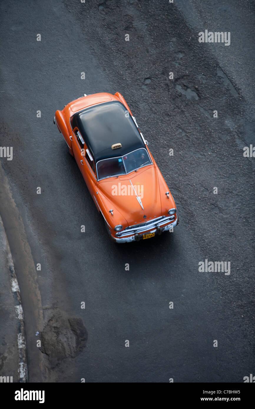 Orange vintage americano auto taxi sul Malecon sea wall, Città dell Avana, Havana, Cuba Immagini Stock