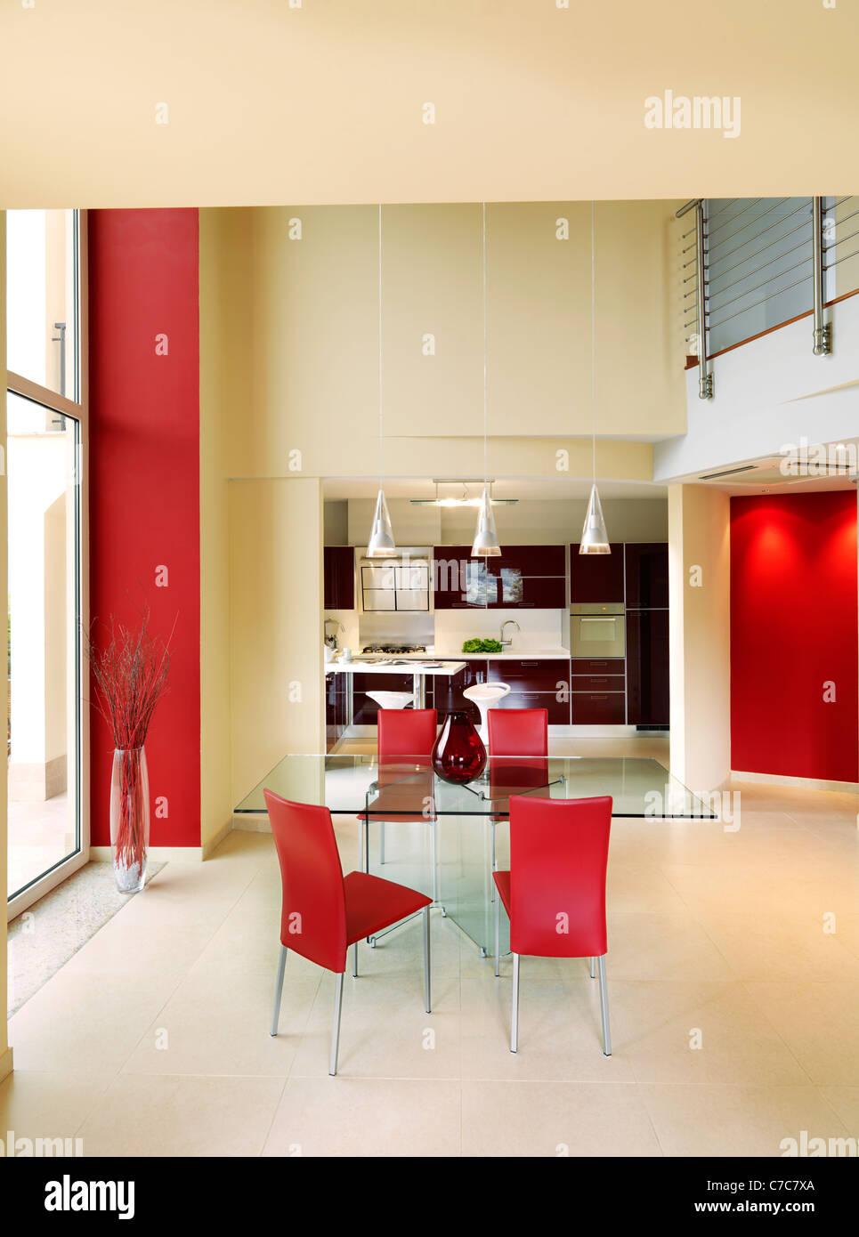 Moderna sala da pranzo con cucina a vista e tavolo di vetro attorno ...