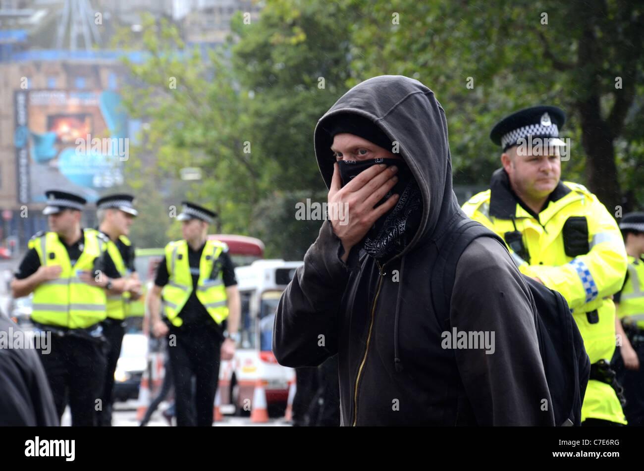 Incappucciato e mascherato protester passeggiate lungo Princes Street di Edimburgo mentre la polizia stanno a guardare Immagini Stock