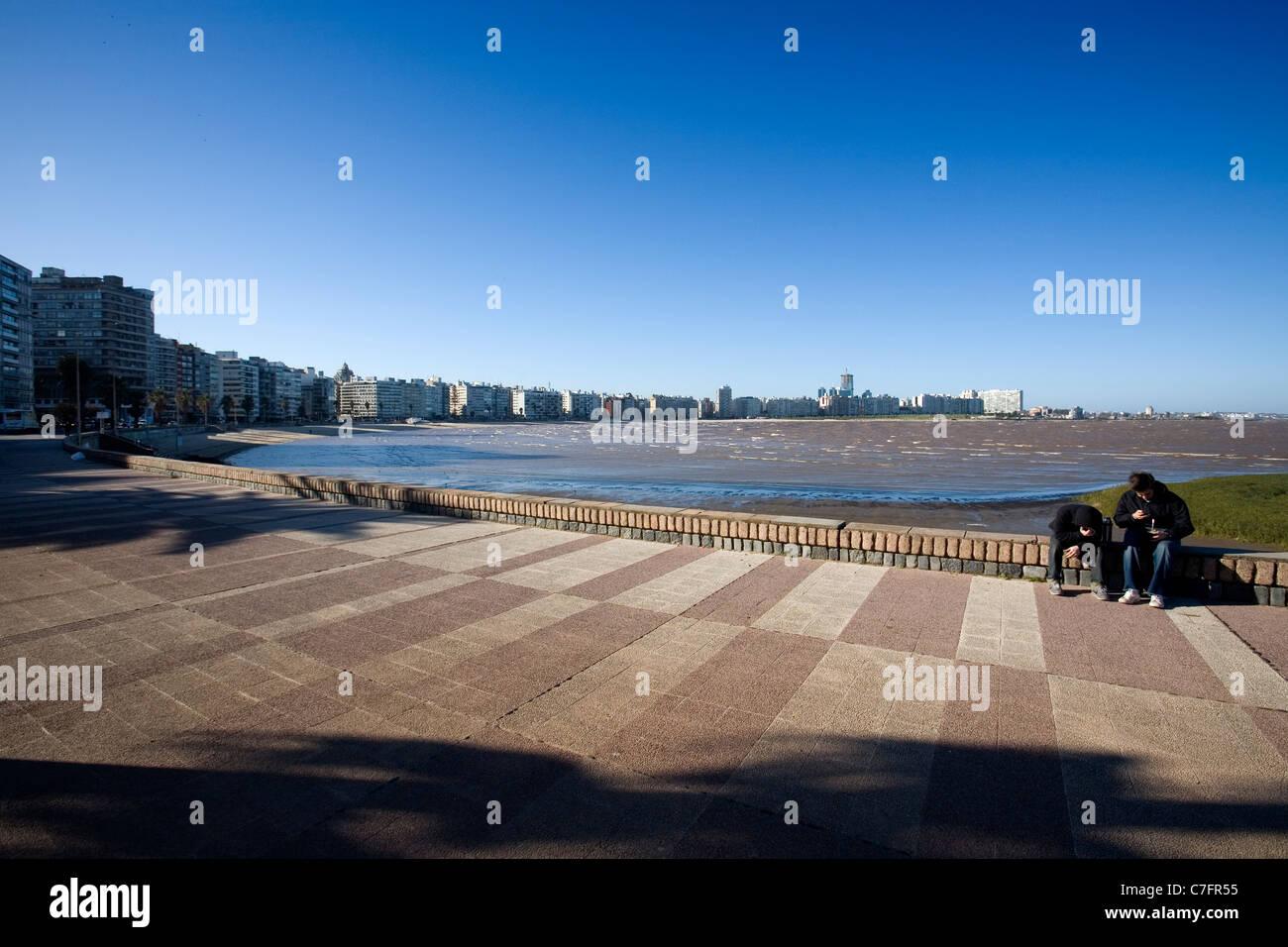 Due ragazzi seduti lungo la Rambla di Montevideo Uruguay Immagini Stock