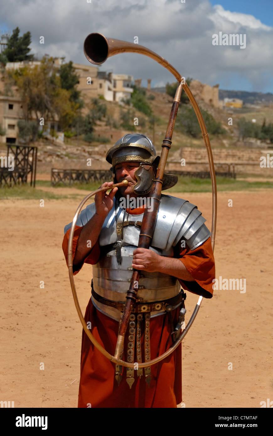 Si tratta di un uomo in uniforme romana la riproduzione di una sorta di tromba nella città di Jerash. Immagini Stock