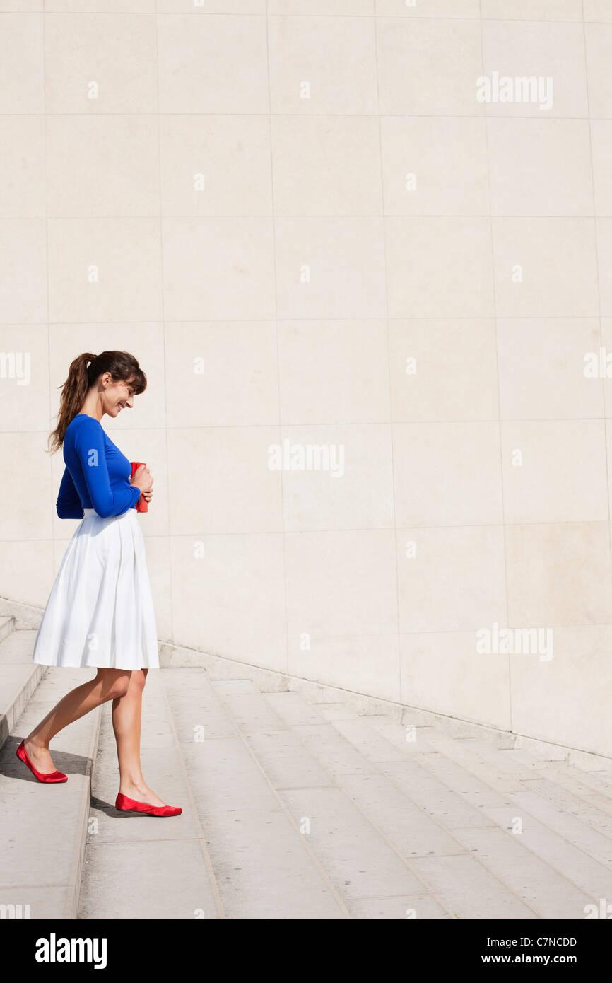 La donna si sta spostando verso il basso le fasi, Parigi, Ile-de-France, Francia Immagini Stock
