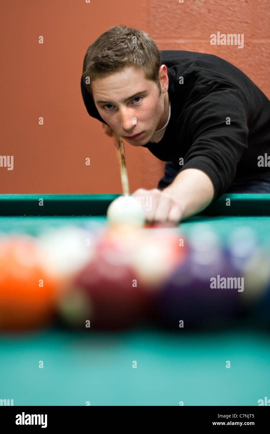 Un giovane uomo linee fino il suo tiro come egli rompe le sfere per l'inizio di un gioco di biliardo. Profondità Foto Stock