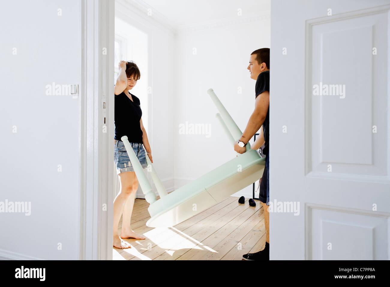 Coppia portando la tabella nella nuova casa Immagini Stock