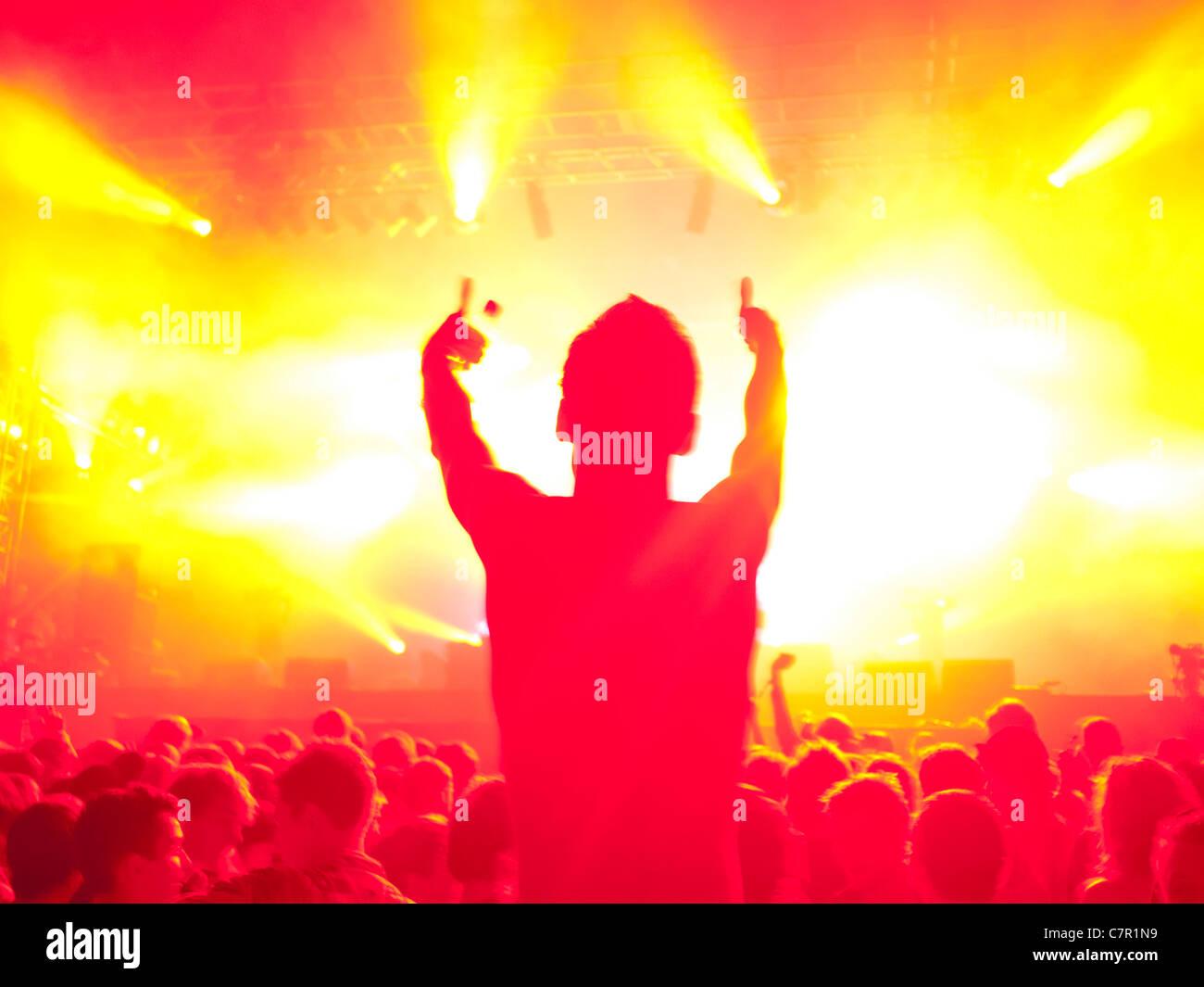 Un ventilatore di musica su someones spalle ad un festival di musica Foto Stock