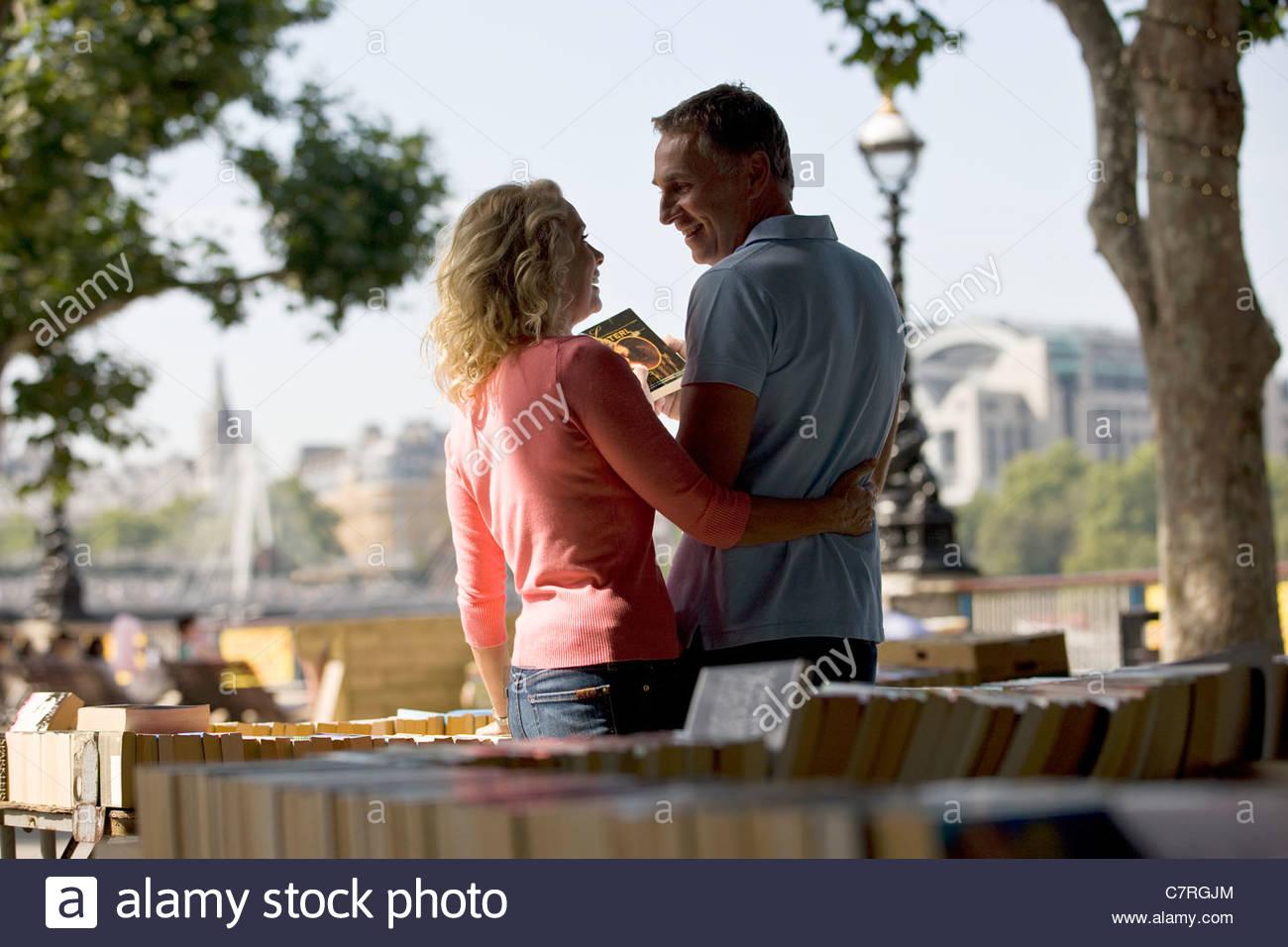 Una coppia di mezz'età guardando i libri ad un libro in stallo Immagini Stock