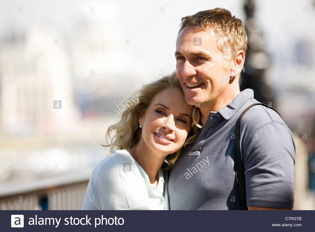 Ritratto di una coppia di mezz'età accanto al fiume Tamigi abbracciando Immagini Stock