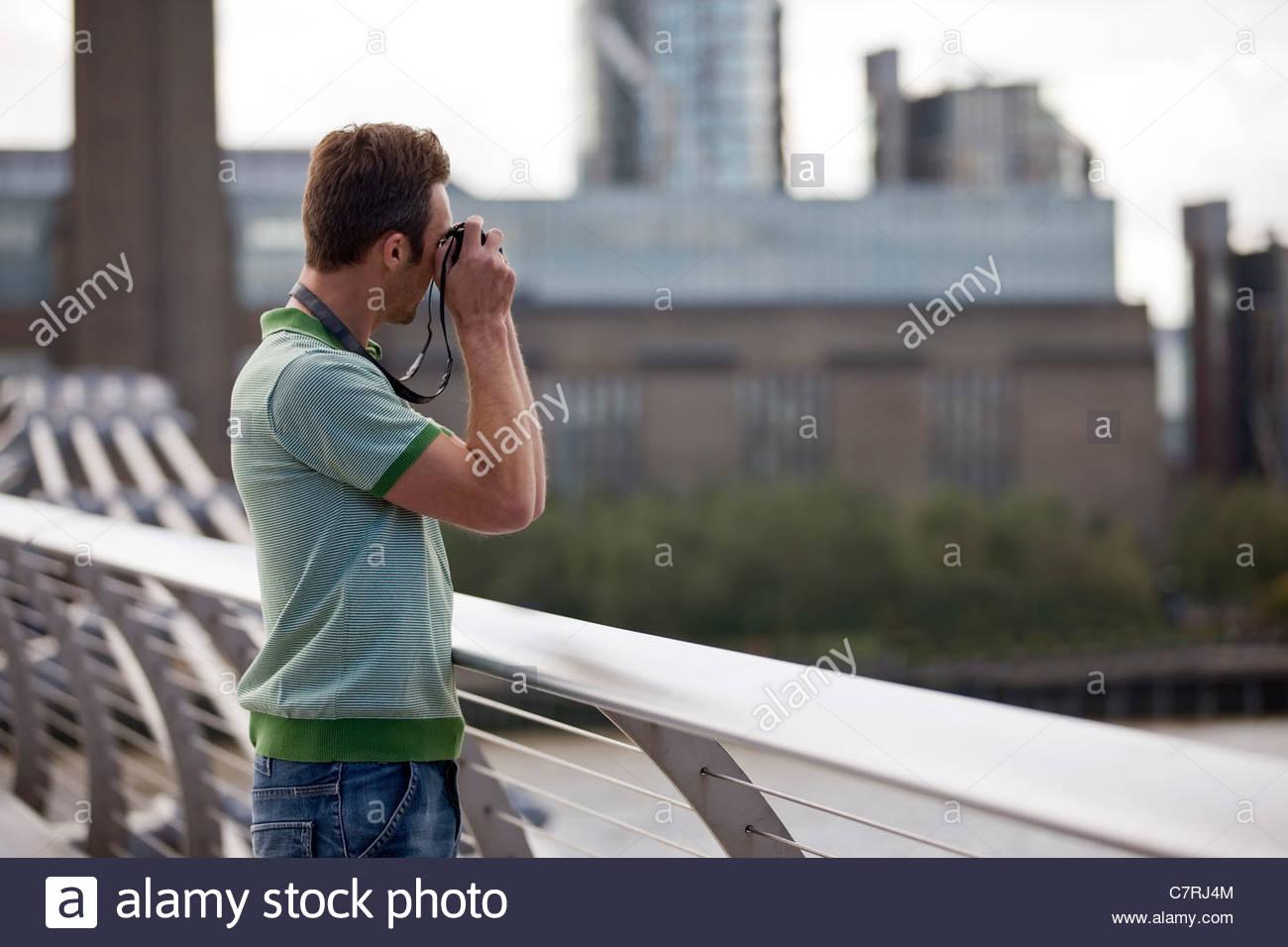 Una metà di uomo adulto in piedi sul Millennium Bridge, prendere una fotografia Foto Stock