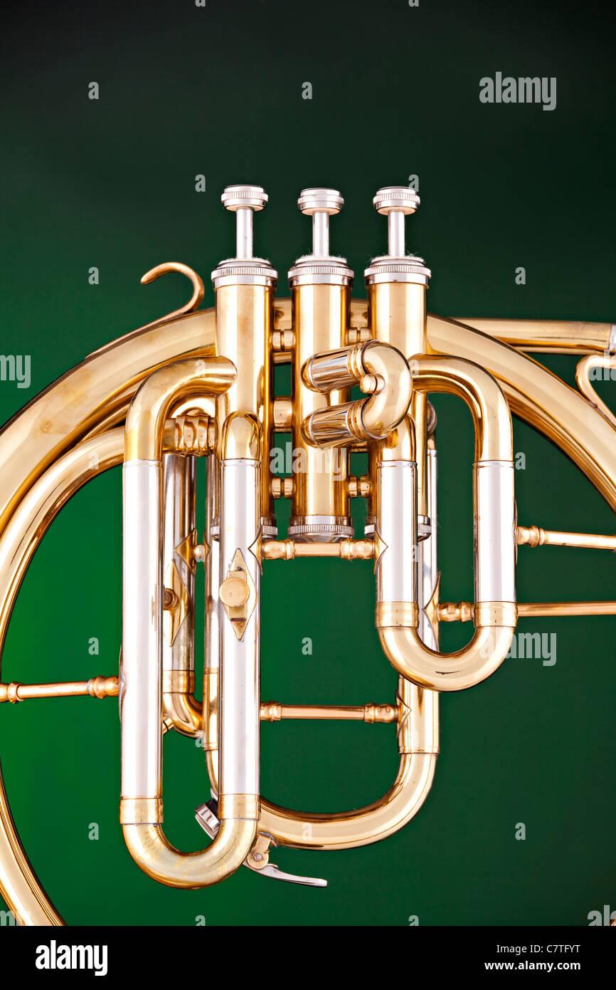 Un antico corno francese o peckhorn isolata contro un faretto sfondo verde.  Immagini Stock 0282a4f37cce