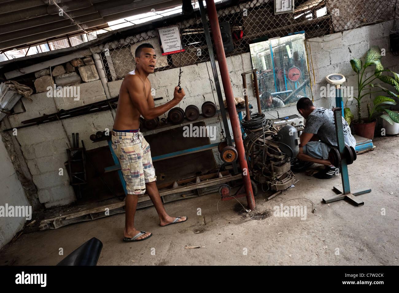 Un giovane uomo cubano non esercizio di fitness con barbells in una palestra di bodybuilding in alamar, Havana, Immagini Stock