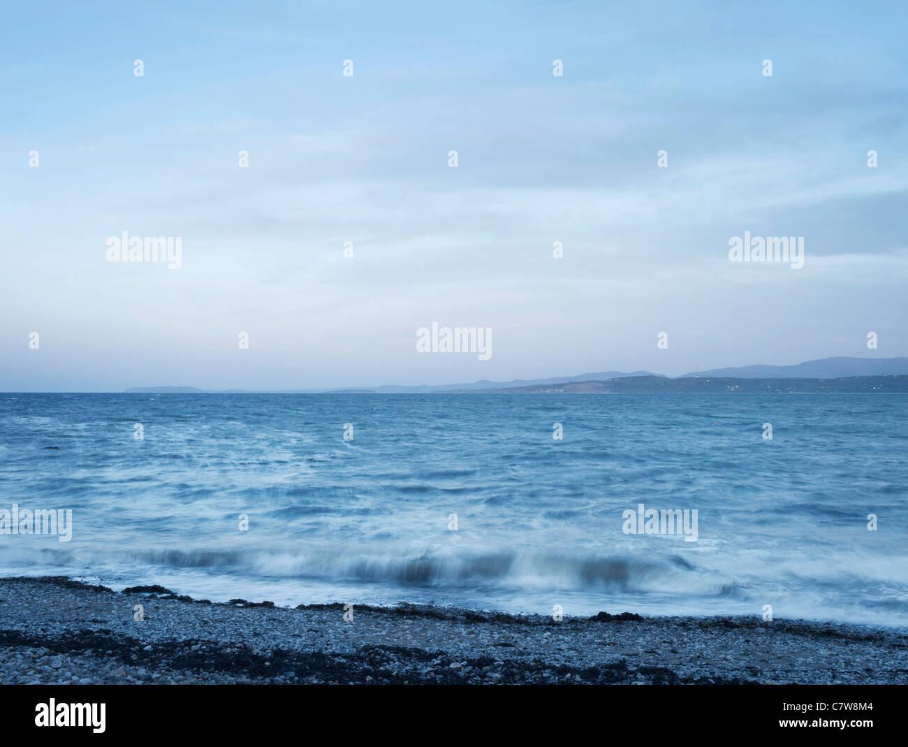 Anglesey seascape al tramonto con la spiaggia di ciottoli, con lo spostamento dei mari e il cielo al tramonto e Immagini Stock
