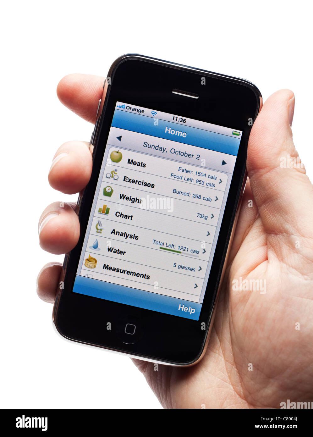Mano che tiene l'iPhone mostra un contatore di caloria app per aiutare con un apporto calorico controllato la Immagini Stock