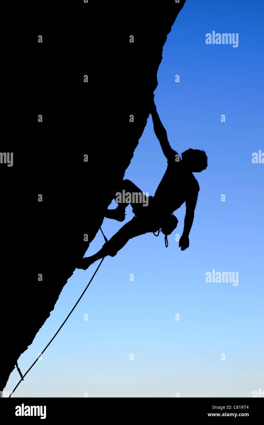 Silhouette di rocciatore salendo una rupe a strapiombo con cielo blu sullo sfondo Immagini Stock