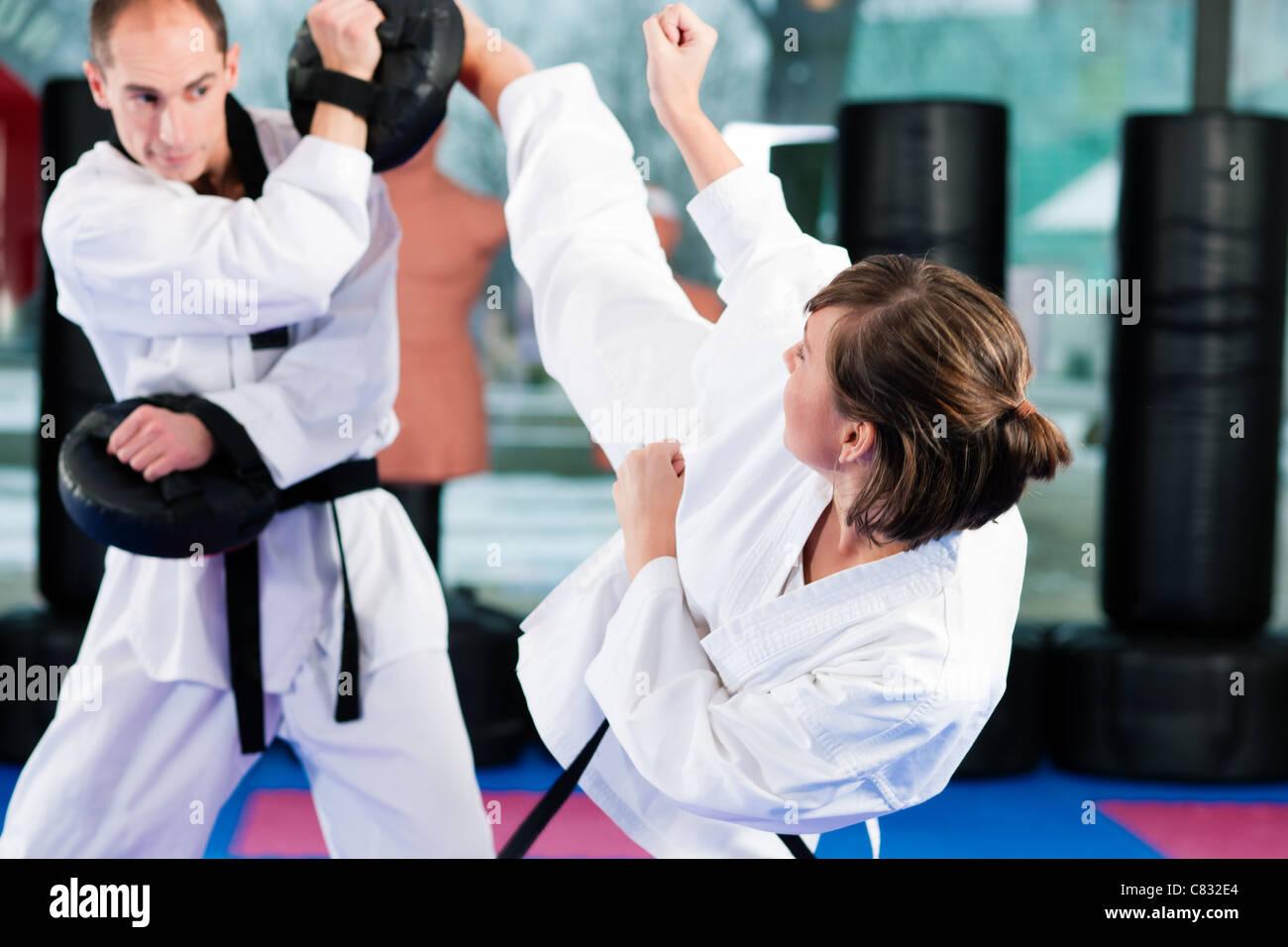 Persone nella palestra di arti marziali formazione esercizio Taekwondo, hanno entrambi una cintura nera Immagini Stock