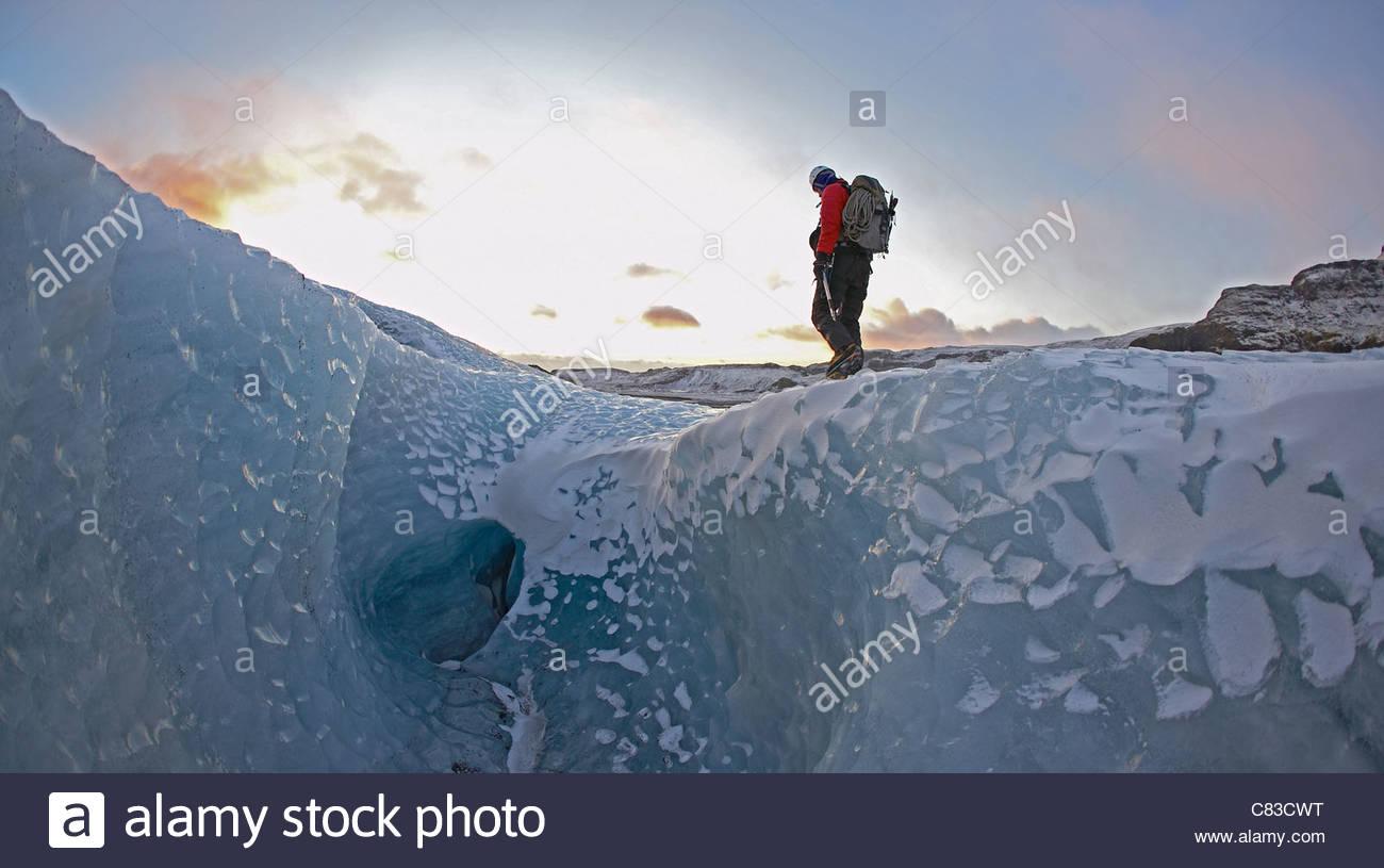 Uomo che cammina sul ghiacciaio Immagini Stock