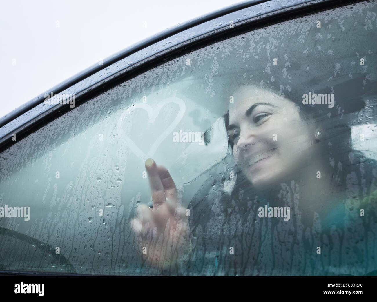 Ragazza adolescente disegno sul bagnato la finestra auto Immagini Stock