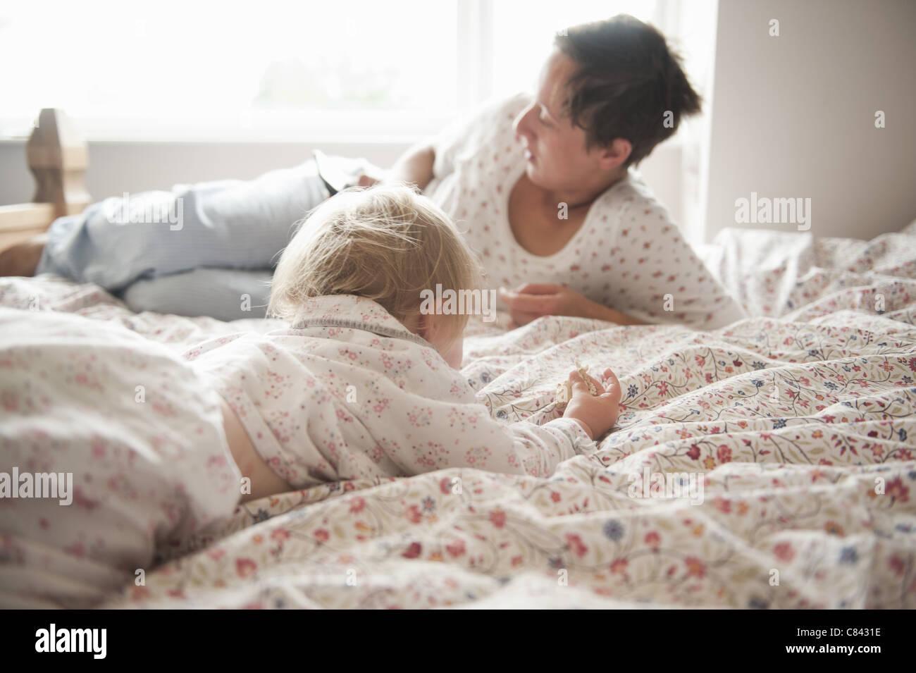 Il Toddler ragazza seduta con la madre a letto Foto Stock