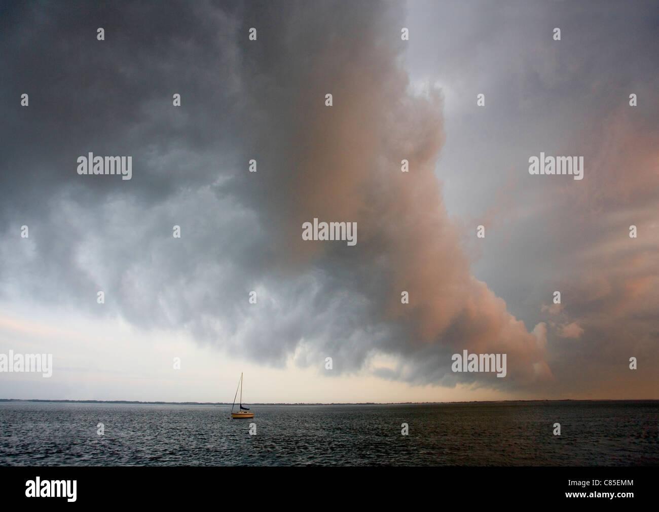 Una drammatica cloud araldi il trascorrere di un tempo come anteriore passa sopra una baia e una barca a vela ormeggiata. Immagini Stock